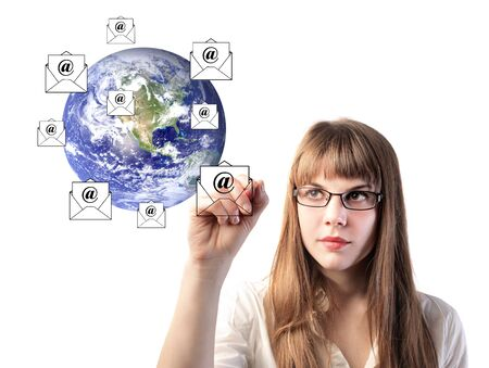 Businesswoman drawing e-mail symbols around the earth photo