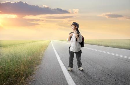 viajero: Ni�o sonriente con mochila caminando sobre una carretera de campo