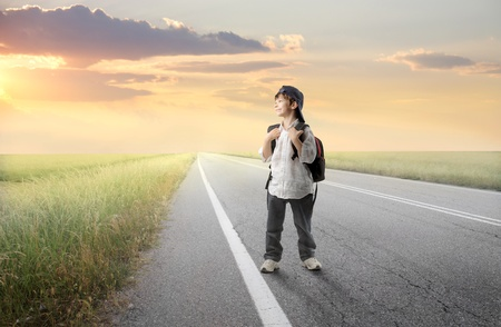 Smiling child with rucksack walking on a countryside road Stock Photo - 8853179