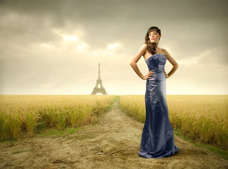 street fashion: Beautiful woman in blue dress with Eiffel Tower on the background