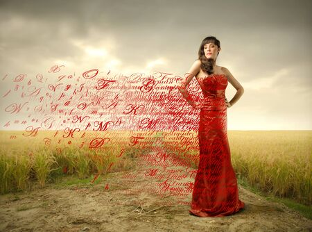 Beautiful woman in red dress with alphabet letters flying away from it photo