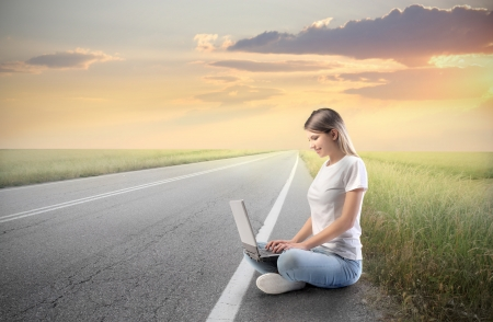 Smiling woman using a laptop on a countryside road photo