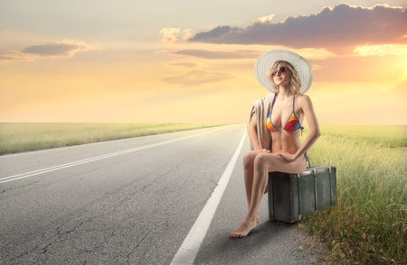 frau mit koffer: Beautiful Woman in Badeanzug sitting on a Suitcase on a Road countryside