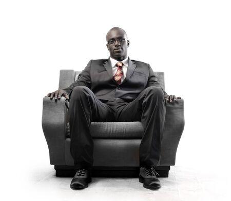 African businessman sitting on an armchair photo