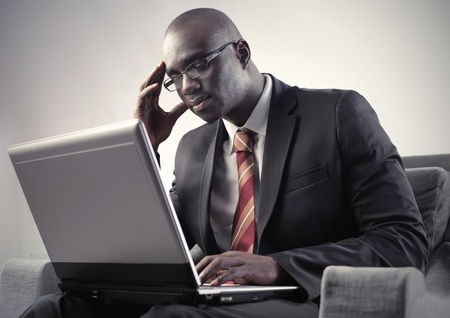 Thoughtful african businessman using a laptop photo