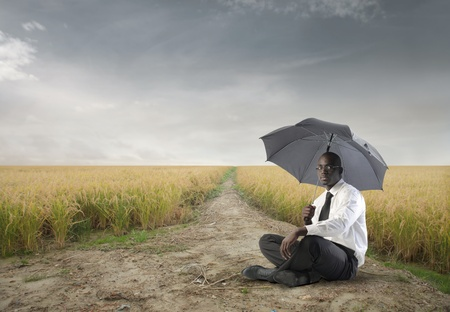 African businessman with umbrella sitting on a field photo