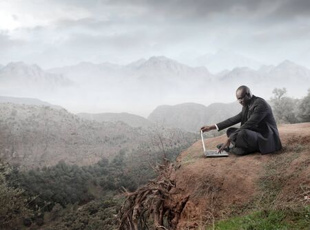 african business man: African businessman using a laptop on a mountain