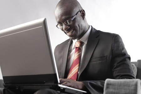 Smiling african businessman using a laptop