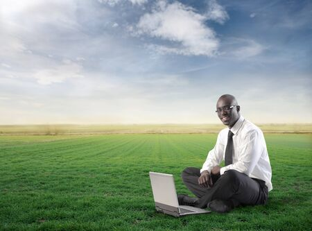 Smiling african businessman using a laptop on a green meadow Stock Photo - 8864231
