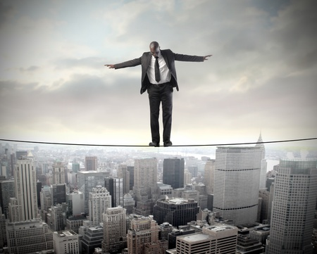 risky: Businessman standing on a cable over a city