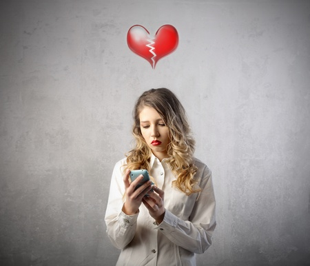 pared rota: Mujer triste con el coraz�n roto, utilizando un tel�fono m�vil