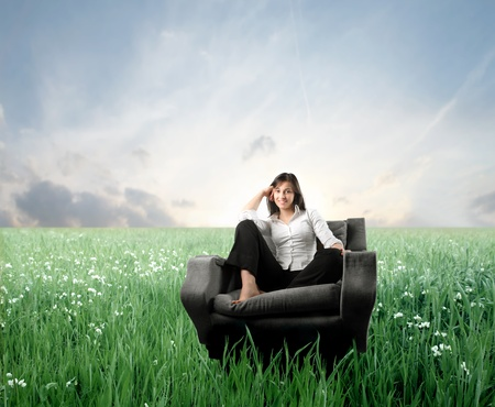 Lächelnde Frau sitzt auf einem Sessel auf einer grünen Wiese