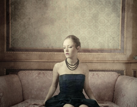Beautiful woman sitting on a sofa photo
