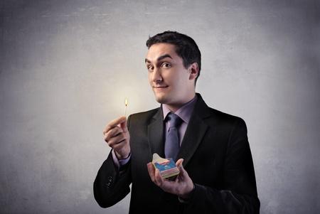 pyromaniac: Businessman holding a match