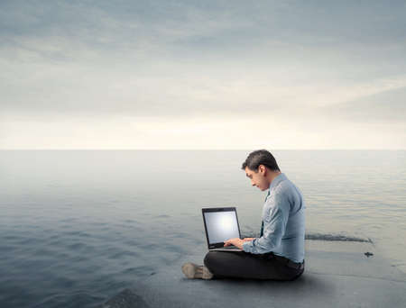 Businessman using a laptop on a wharf Stock Photo - 8999970