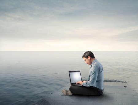 wharf: Businessman using a laptop on a wharf