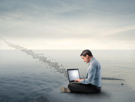 Businessman using a laptop on a wharf with numbers flying away from it Stock Photo