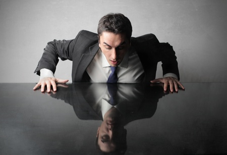 reflection in mirror: Astonished businessman lookng at his reflex on a table Stock Photo