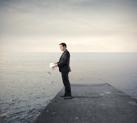 earn money: Businessman throwing some banknotes in a lake