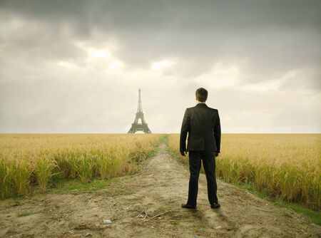 distant: Businessman on a wheatfield with Eiffel Tower on the background