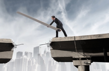 risky job: Businessman rebuilding a broken bridge