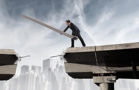 Zakenman wederopbouw een gebroken brug Stockfoto