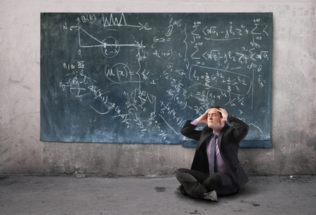 Stressed businessman with blackboard on the background Stock Photo