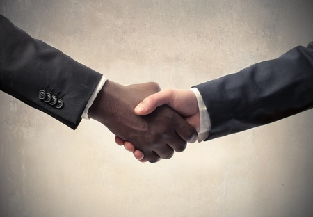 Black businessmans hand shaking white businessmans hand photo