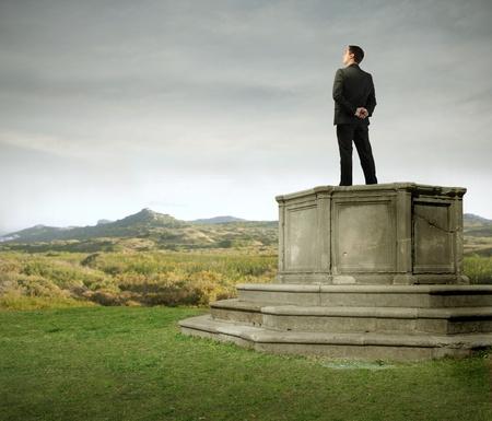 Businessman standing on a pedestal