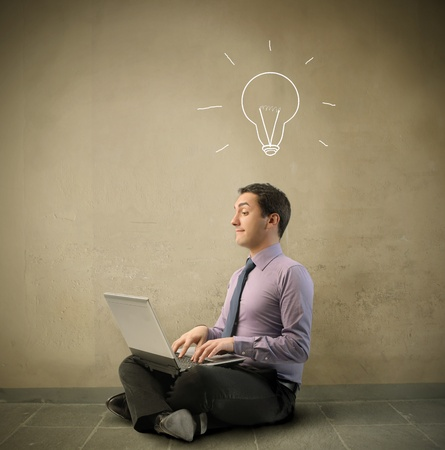 Businessman using a laptop with light bulb over his head photo
