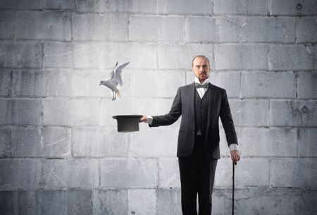 magician hat: Magician with bird flying away from his cylinder hat Stock Photo