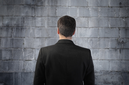 impediment: Businessman standing in front of a wall