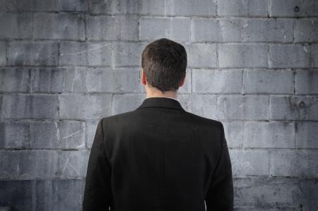 Zakenman die zich voor een muur bevindt Stockfoto