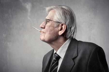 Senior businessman smoking a cigarette photo