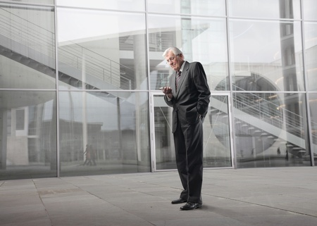 Senior businessman using a mobile phone with office building on the background photo