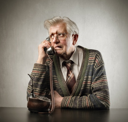 Worried senior man talking to telephone photo