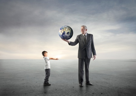 assign: Senior businessman lending the Earth to a child Stock Photo