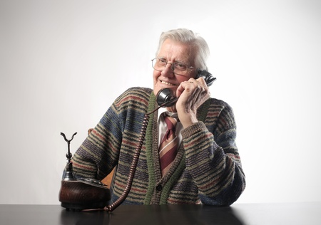 Smiling senior man talking to telephone photo