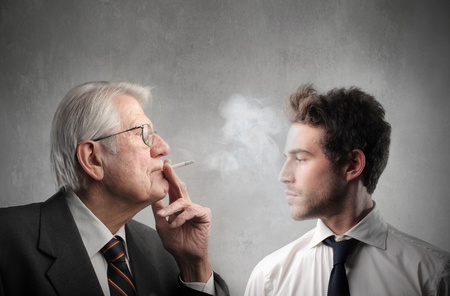 disdain: Senior businessman smoking in front of a younger one