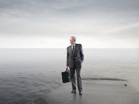 Senior man walking on a seashore photo