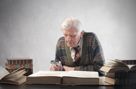 Senior man examining a book with a mangifying glass photo