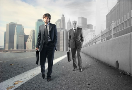 Young businessman and older one walking on a city street photo