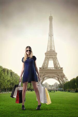 Schöne Frau mit vielen Einkaufstaschen mit Eiffelturm im Hintergrund
