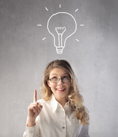 easy: Smiling businesswoman having an idea with light bulb over her head