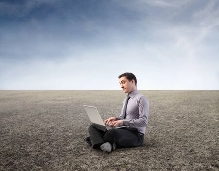 Businessman using a laptop in a desert photo