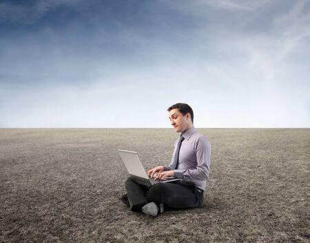 Zakenman met behulp van een laptop in een woestijn