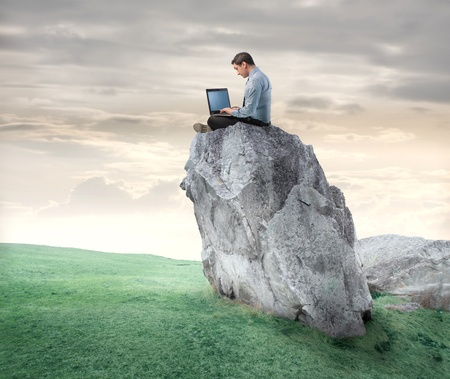 Businessman sitting on a rock and using a laptop Stock Photo - 9138560