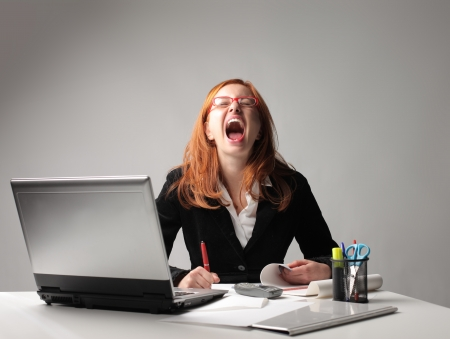 despair: Nervous businesswoman screaming at the office Stock Photo