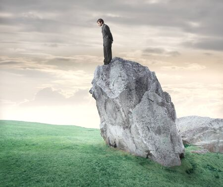 Businessman standing on a rock and looking downwards photo