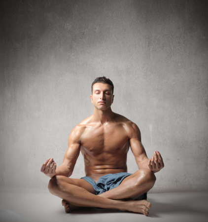Handsome young man doing yoga exercise photo